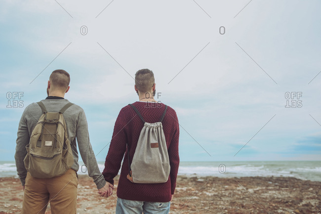 Back view of young gay couple with backpacks standing hand in hand on the beach looking at the sea