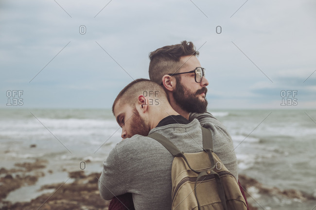 Young gay couple hugging on the beach