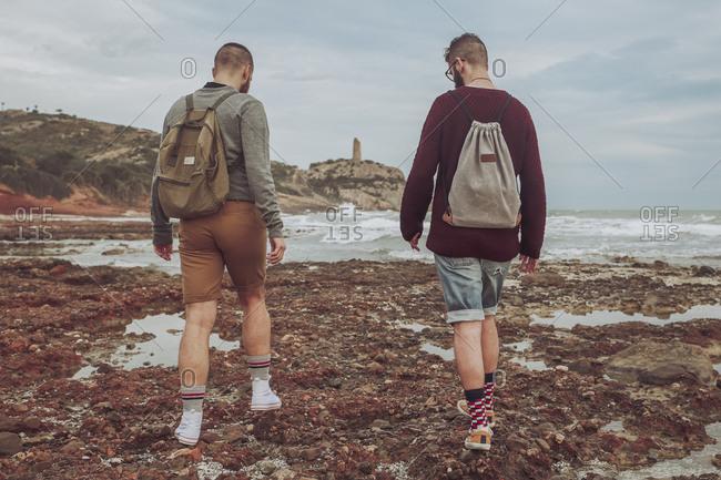 Spain- Oropesa del Mar- two young men walking on stony beach