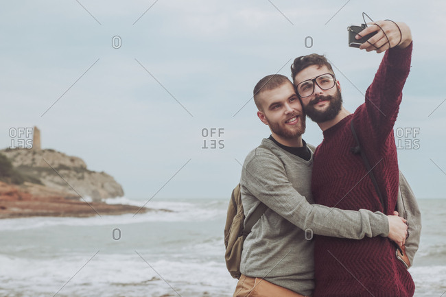 Spain- Oropesa del Mar- gay couple taking selfie in front of the sea