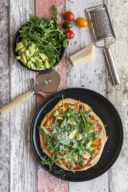 Vegetarian pizza with avocado- rocket- tomatoes and parmesan