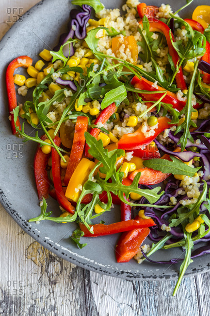 Glass of rainbow salad with bulgur- rocket and different vegetables and bowls with ingredients- close-up