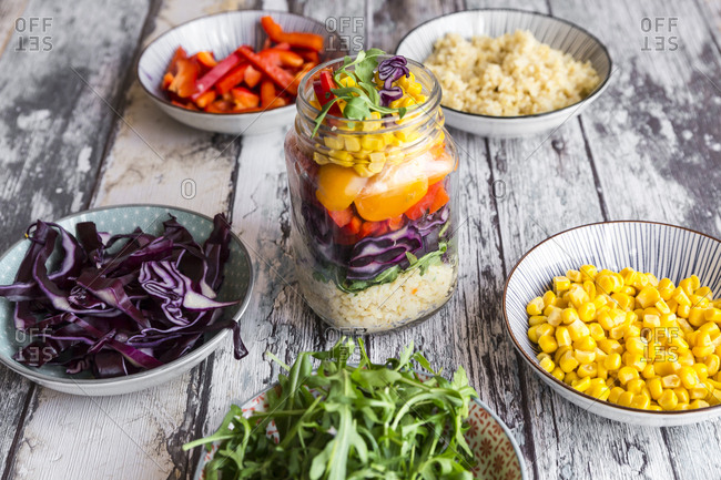 Glass of rainbow salad with bulgur- rocket and different vegetables and bowls with ingredients