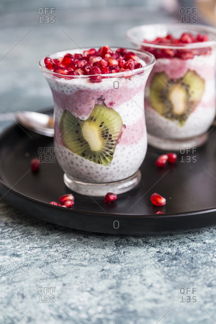 Two glasses of chia pudding with heart-shaped kiwi slices and pomegranate seed