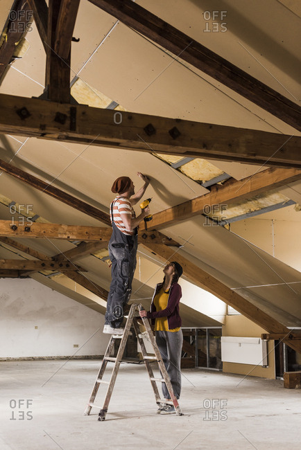 Young man and woman mounting insulation on construction site