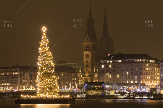 Hamburg, Germany - December 9, 2016: Lighted Christmas tree at Binnenalster with town hall in the background