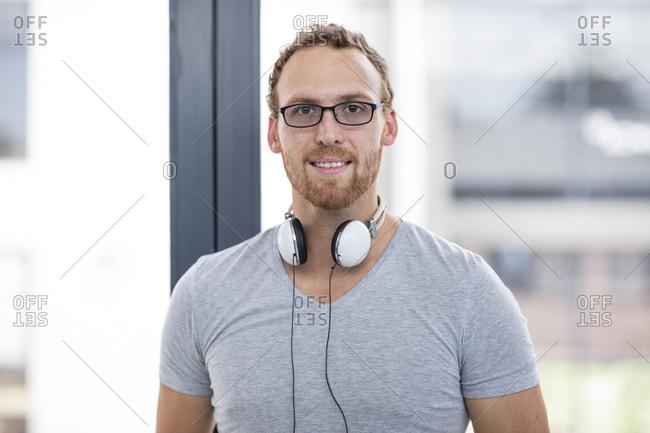 Young man with headphones around his neck- portrait