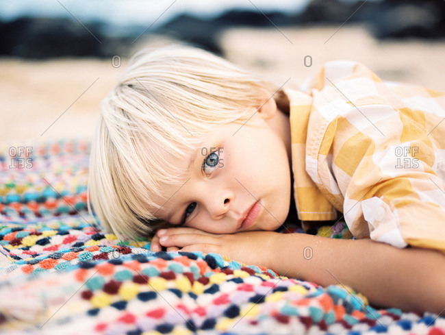 Young boy laying on colorful beach blanket