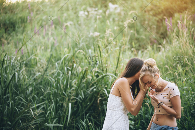 Young woman whispering something to her girlfriend