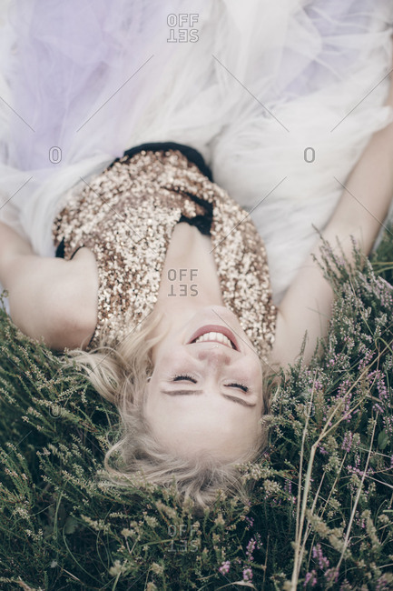 Young blond woman lying in the grass