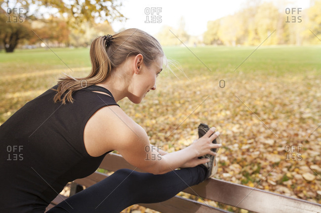 Young woman stretches before jogging in the park