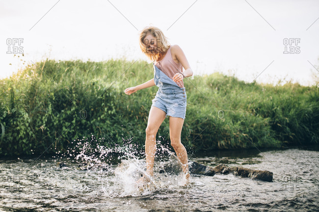 Young woman kicks water in a brook