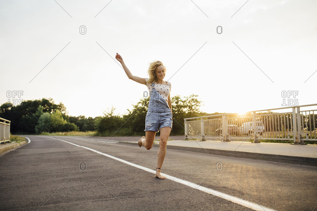 Young woman dancing with joy on the road