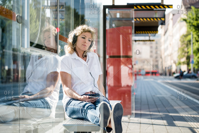 Woman in casual outfit sitting on bus bench listening music