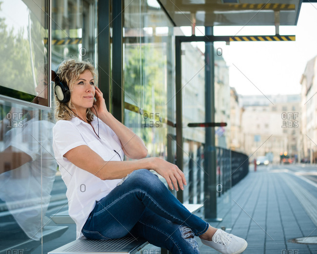 Joyous lady wearing headphones, listening to music while sitting on bus bench.