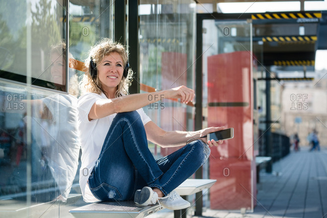 Lively woman tuned into music at the bus stop. People and leisure concept.