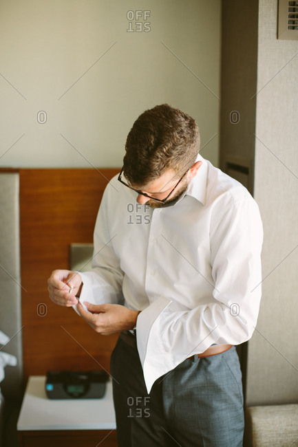 A groom buttoning his cuff