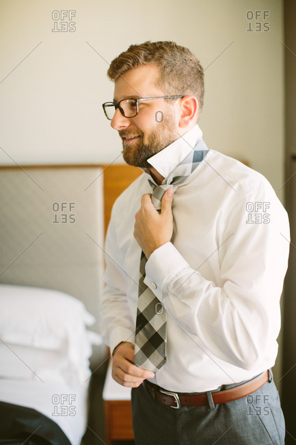 Smiling groom working on his tie