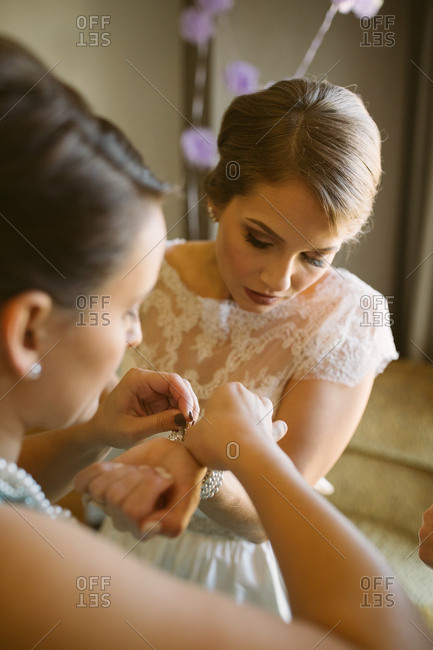 A woman helping bride with jewelry
