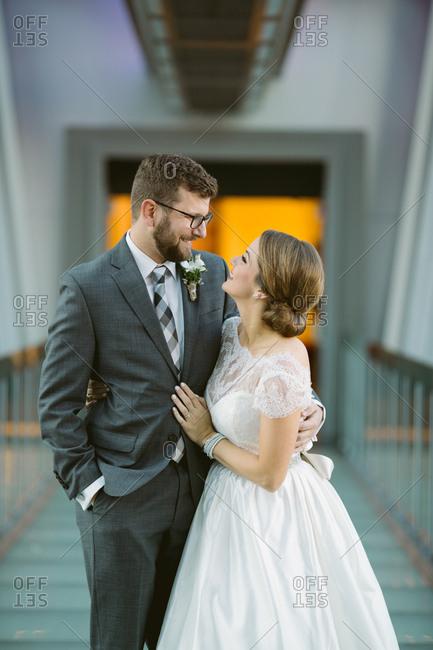 Bride and groom embracing on sky bridge