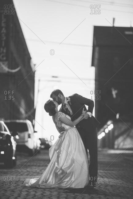 Bridal couple kissing in the street