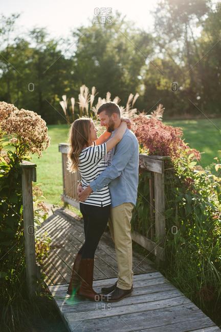 Couple embracing on rural wood bridge