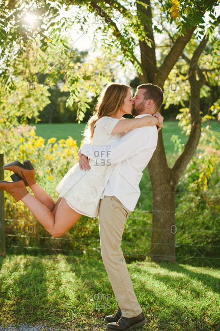 Woman leaping while kissed by man