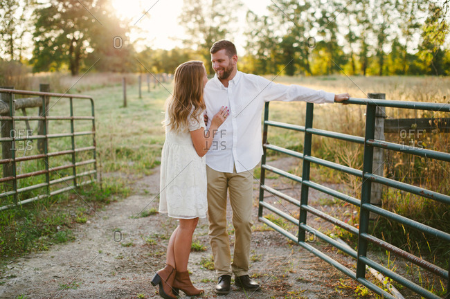 Couple embracing by rural gate