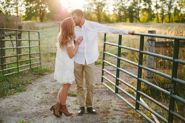 Couple kissing by rural gate