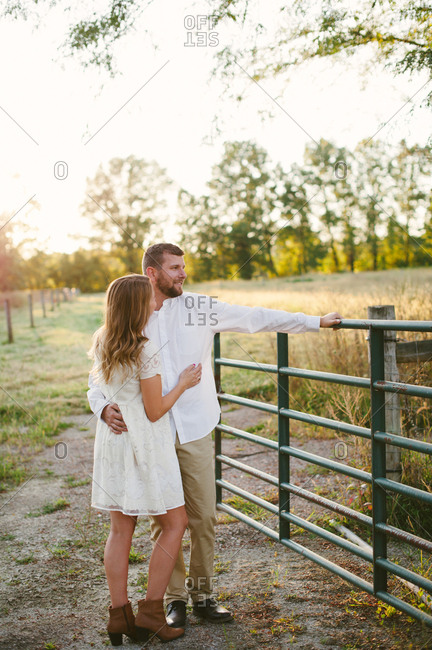 Couple in embrace by rural gate