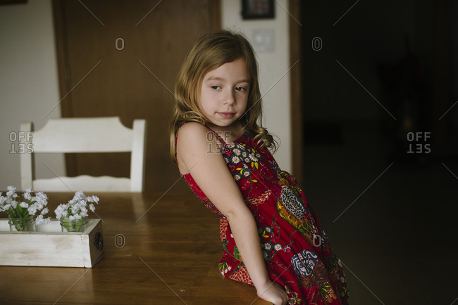 Girl leaning against a dining table