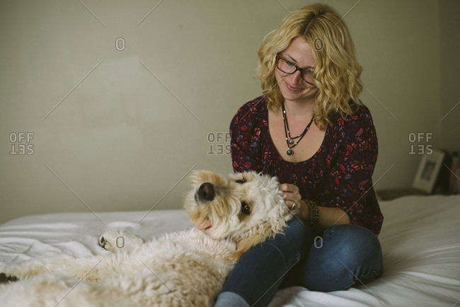 Dog lying on woman on bed