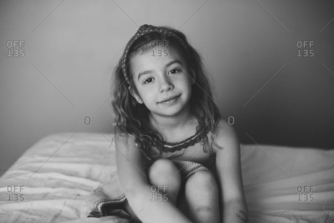 Girl with content smile on bed