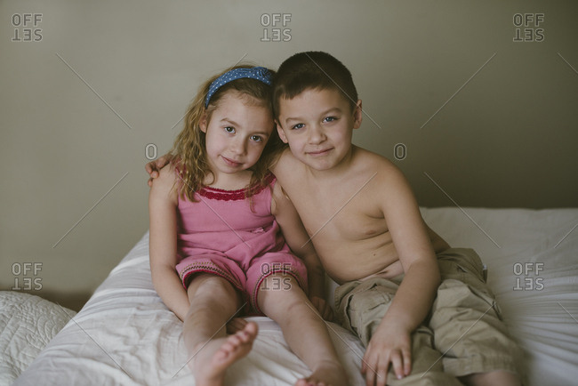 A girl and boy hugging on bed