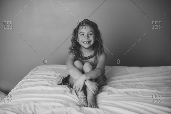 Smiling girl sitting alone on bed