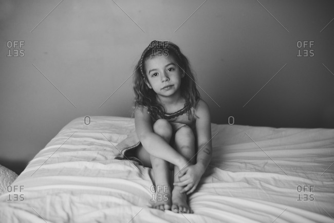 A girl sitting still on bed