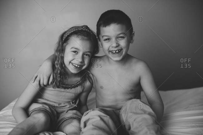 Laughing siblings on a bed together
