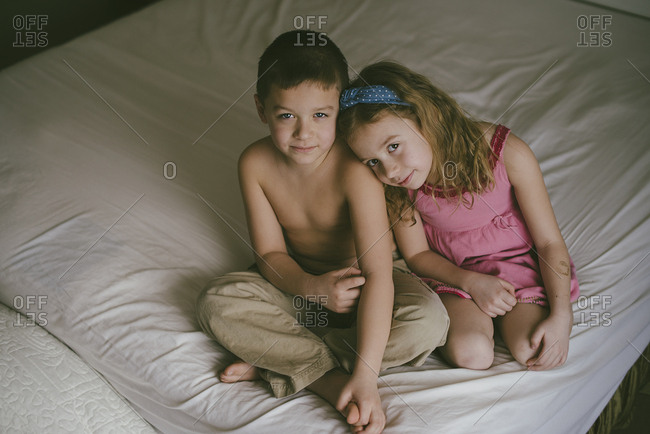 Girl leaning on boy on bed