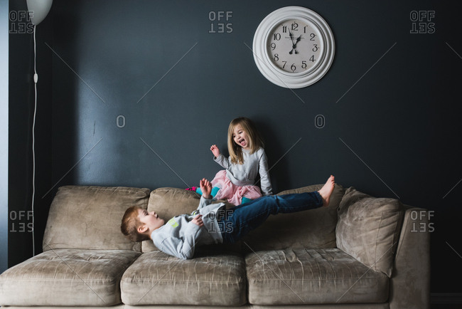 Two young siblings playing on sofa