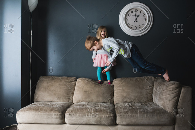 Girl watches brother dive on couch