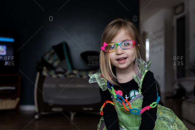 Young girl wearing colorful eyeglasses and princess dress