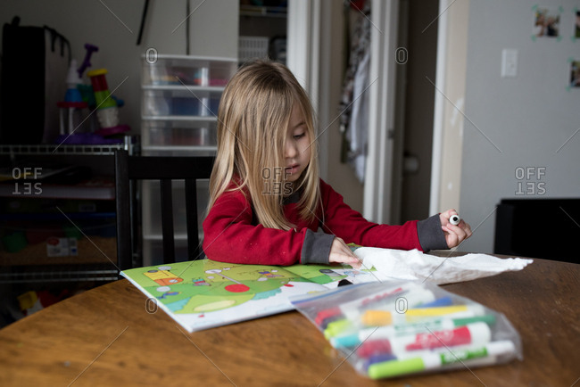 Girl playing with wipe off markers and book