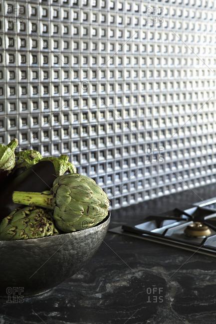 Artichokes in bowl against textured kitchen backsplash
