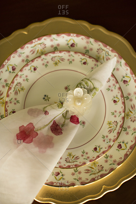 Overhead view of delicate flower patterned place setting with napkin