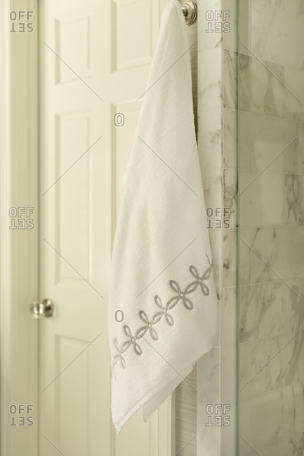 Embroidered towel hanging on hook in bathroom