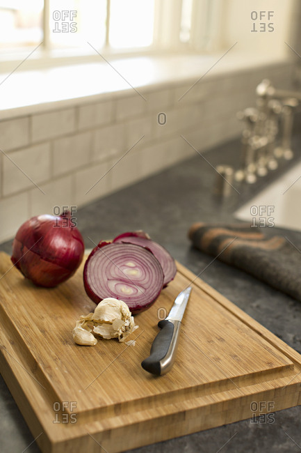 Red onions and garlic on wooden cutting board