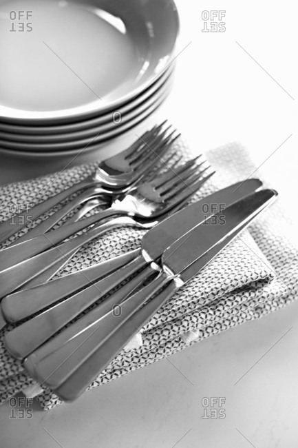 Cutlery and dishes with napkins on table