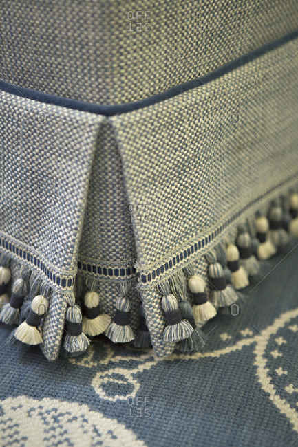 Close-up of tasseled skirt on piece of furniture