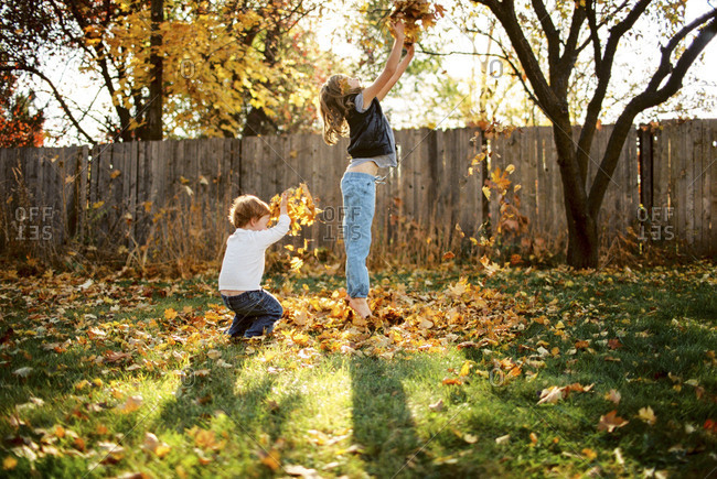 Girl and boy tossing fall leaves