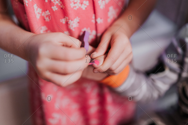 Girl painting little brother's fingernails in a bathroom